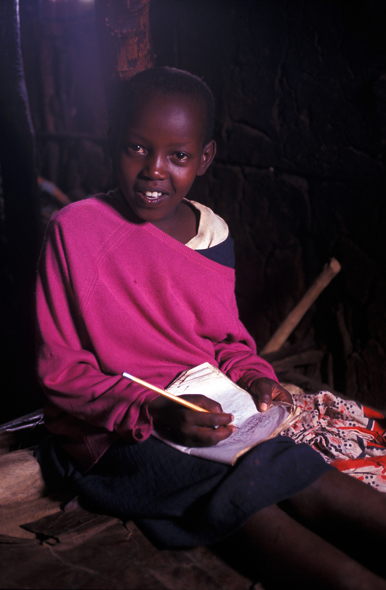 A child struggles to do his school homework in a dark, smokey Maasai hut, Kenya
