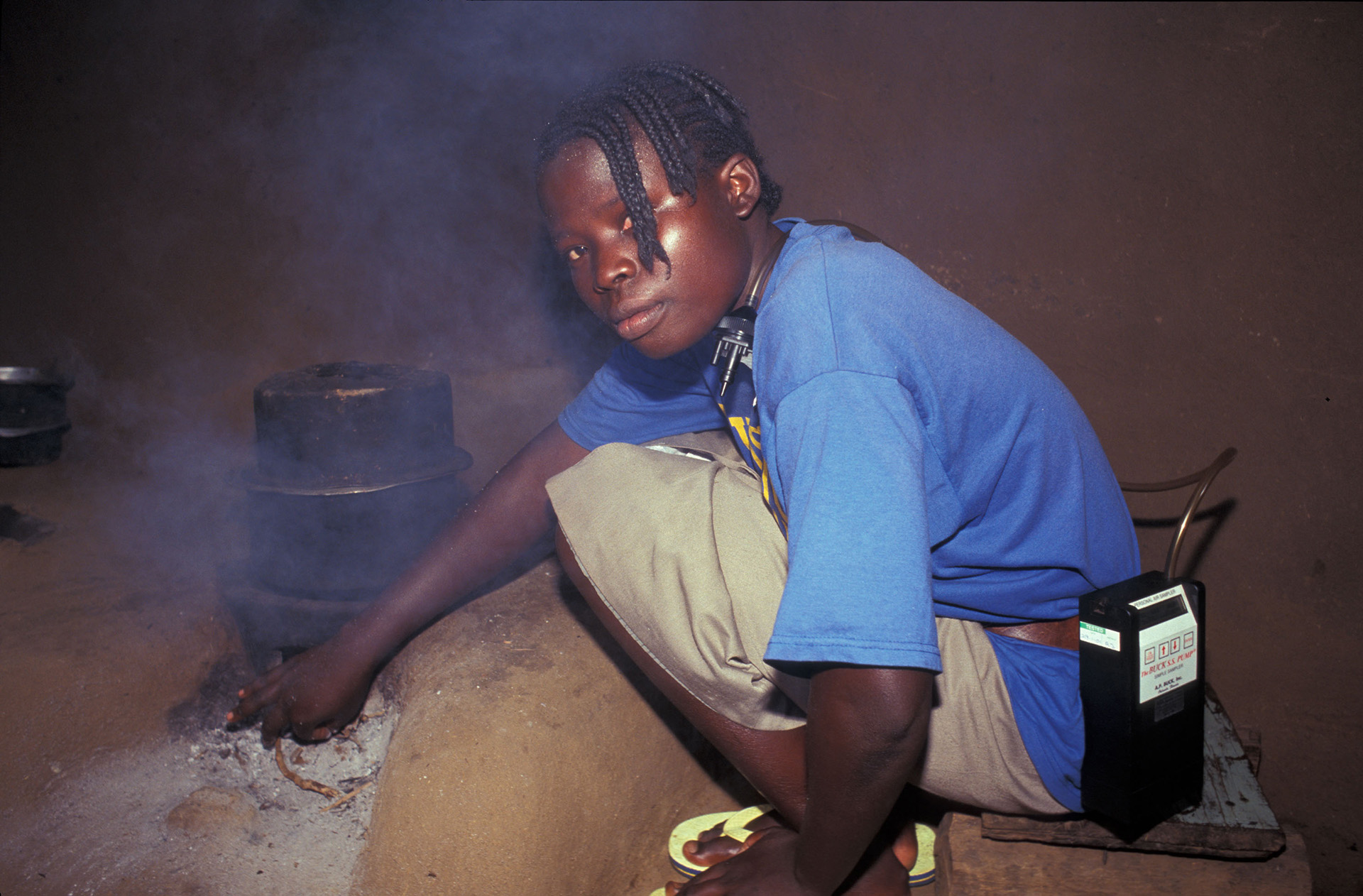 A Kenyan woman wearing a pump and cyclone used for sampling the air she is breathing in order to measure exposure to small particulate matter