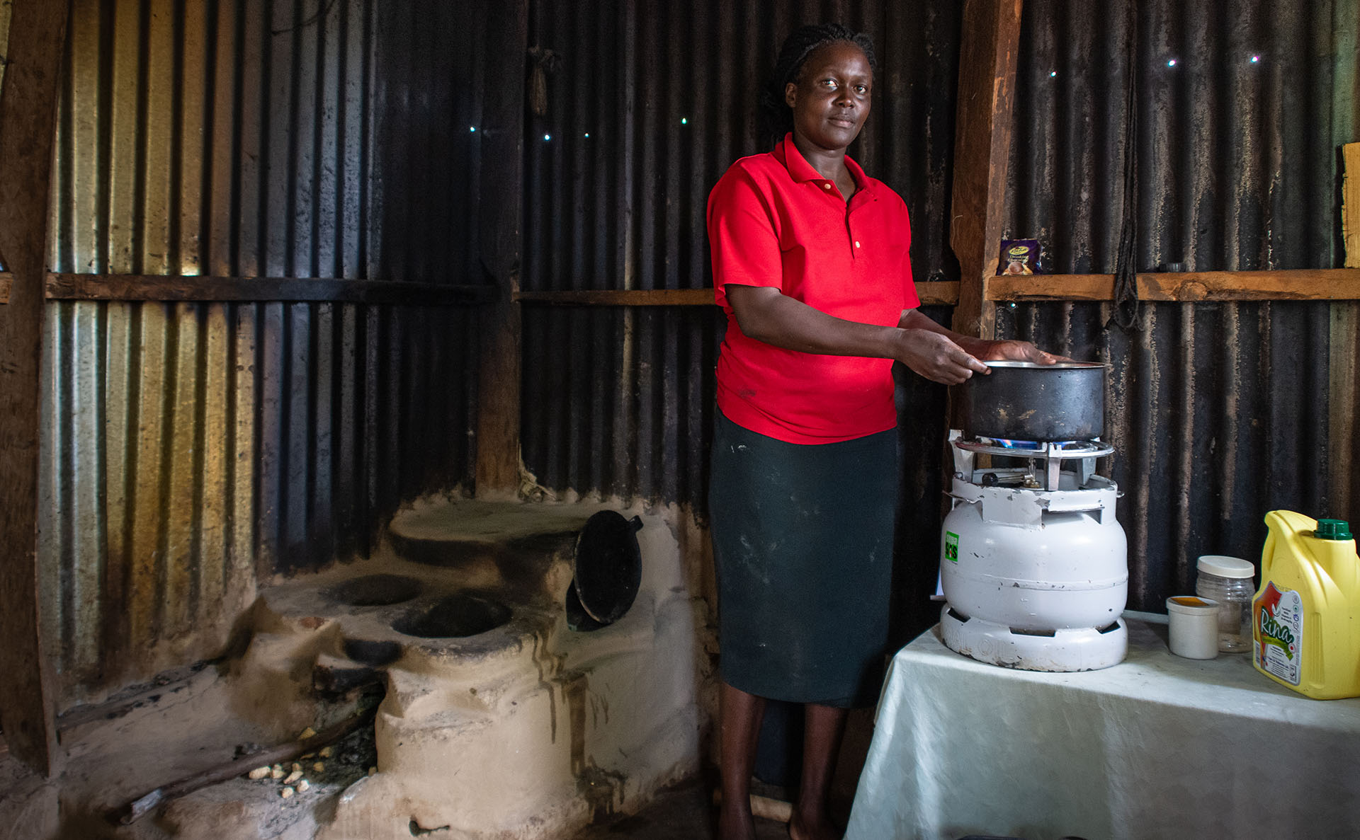 A woman prepares food on an LPG cooker in here home, bit still uses the traditional wood stove for some purposes. This so-called 'stacking' for a variety of reasons, including cost and availability of LPG, and families getting used to using the new fuel for all of their cooking, but it does mean the kitchen is still much more polluted that if LPG was used exclusively