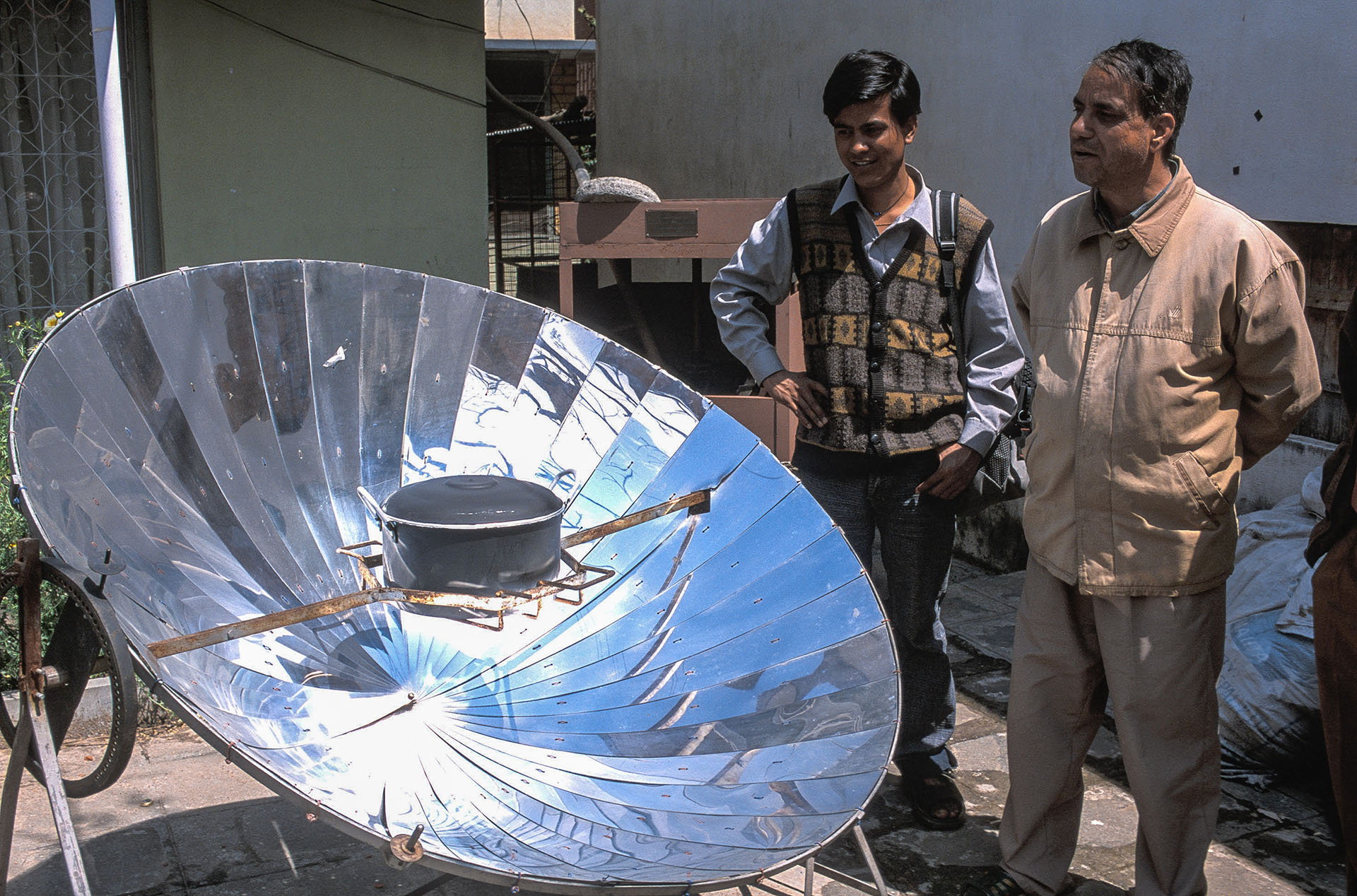 A parabolic solar cooker which reflects and concentrates the sun's radiant heat onto the pot